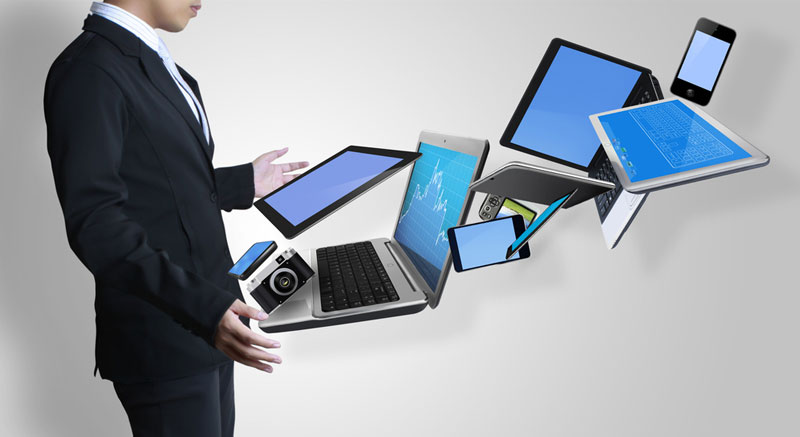 Business man juggling laptop, tablet and mobile phone responsive web design technology